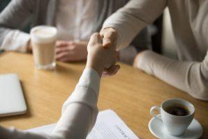 par-handshaking-executiva-fazer-negocio-em-cafe-cima-vista_1163-5141